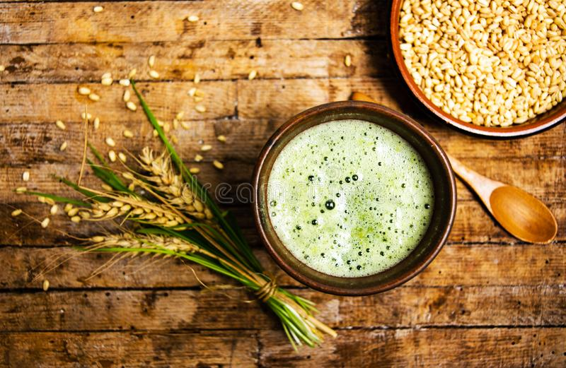 Wheat grass detox smoothie on a wooden table. Wheat grass detox smoothie and branch on a wooden table royalty free stock image