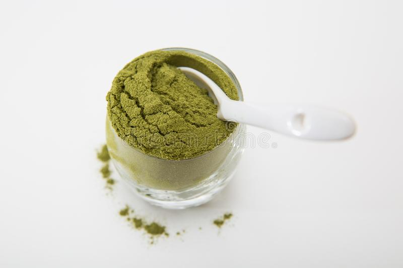 Wheat grass green powder is a healthy supplement to add vitamins and minerals to your diet. Wheat grass green powder, isolated on a white background. Wheat royalty free stock photo