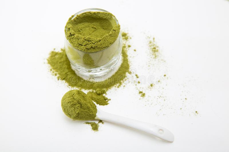 Wheat grass green powder is a healthy supplement to add vitamins and minerals to your diet. Wheat grass green powder, isolated on a white background. Wheat royalty free stock images