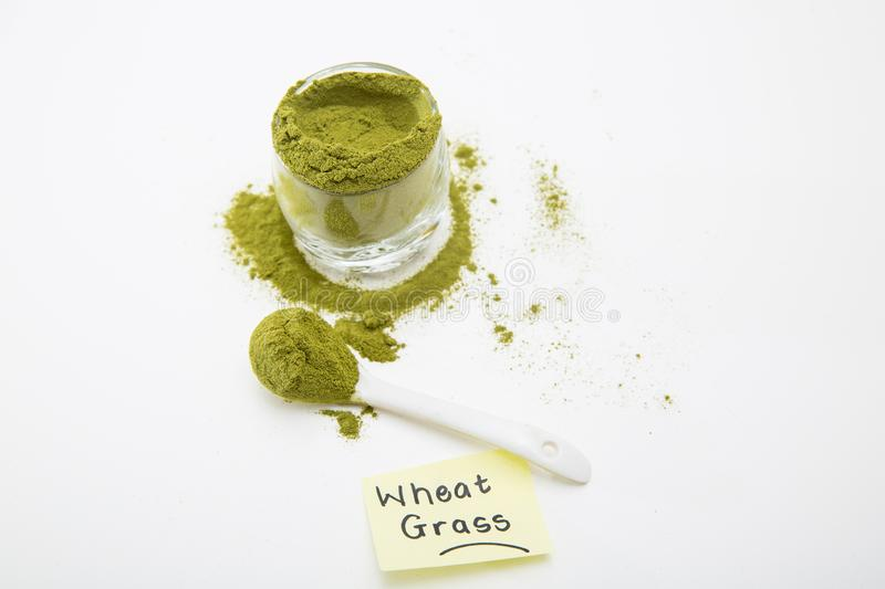 Wheat grass green powder is a healthy supplement to add vitamins and minerals to your diet. Wheat grass green powder, isolated on a white background. Wheat royalty free stock photos