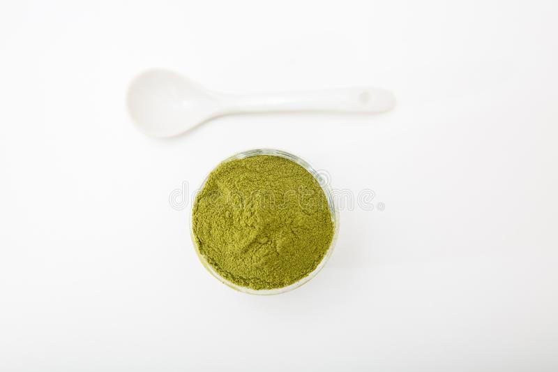 Wheat grass green powder is a healthy supplement to add vitamins and minerals to your diet. Wheat grass green powder, isolated on a white background. Wheat royalty free stock photography