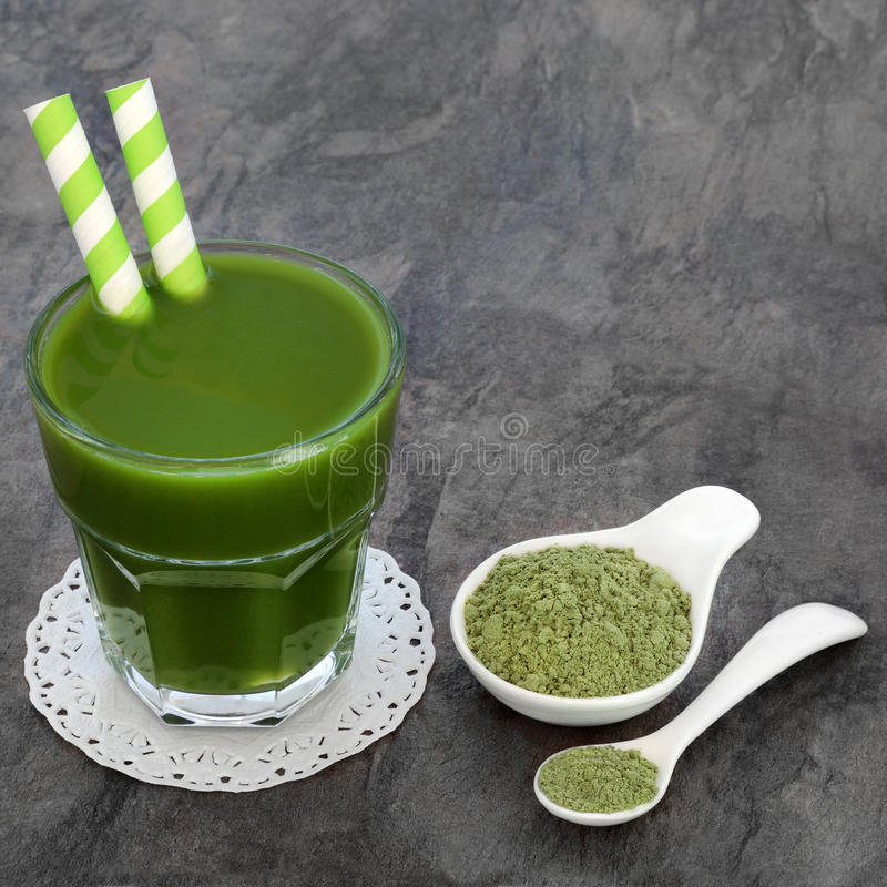Wheat Grass Health Drink. Wheat grass heath drink with supplement powder in a porcelain bowl and spoon royalty free stock image