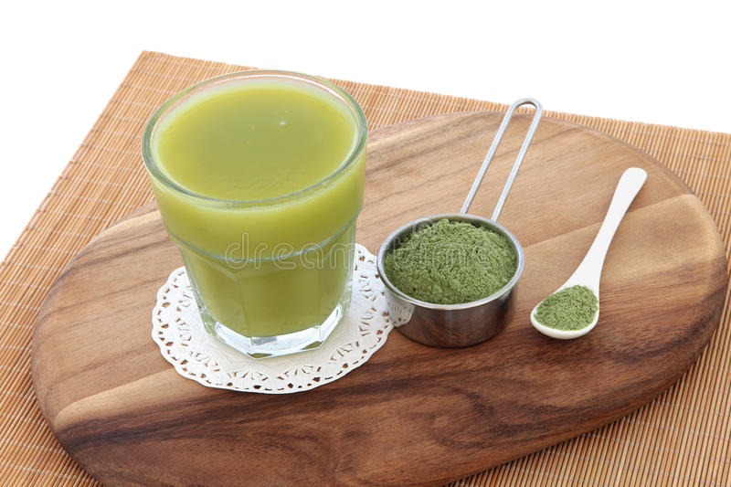 Wheat Grass Health Drink. With powder in scoop and spoon on a maple wood board over bamboo and white background. Also used by body builders, in weight training royalty free stock image