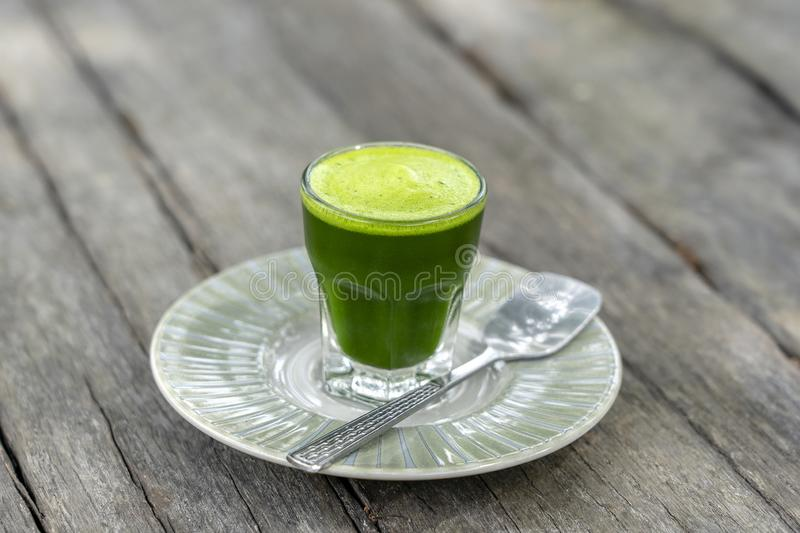 Wheat grass juice natural drink with fresh wheatgrass in glass on old wooden table background. Organic healthy organic green detox. Wheat grass juice natural stock photo