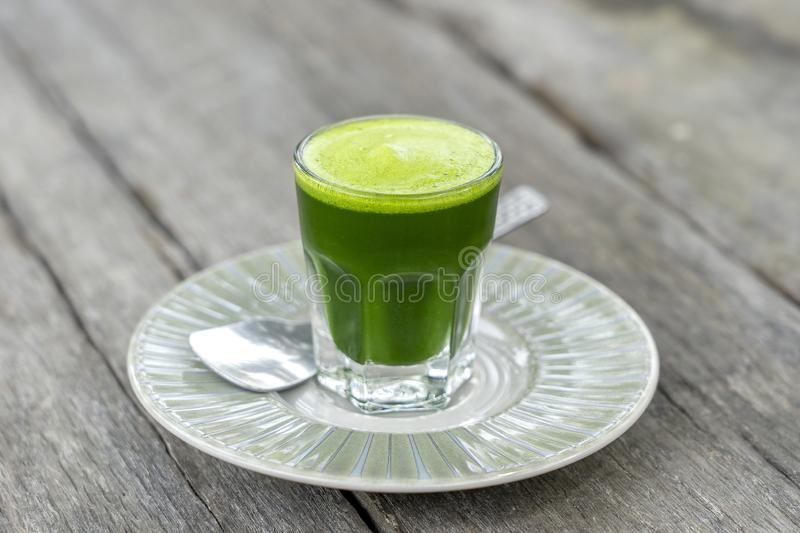 Wheat grass juice natural drink with fresh wheatgrass in glass on old wooden table background. Organic healthy organic green detox. Wheat grass juice natural royalty free stock photo