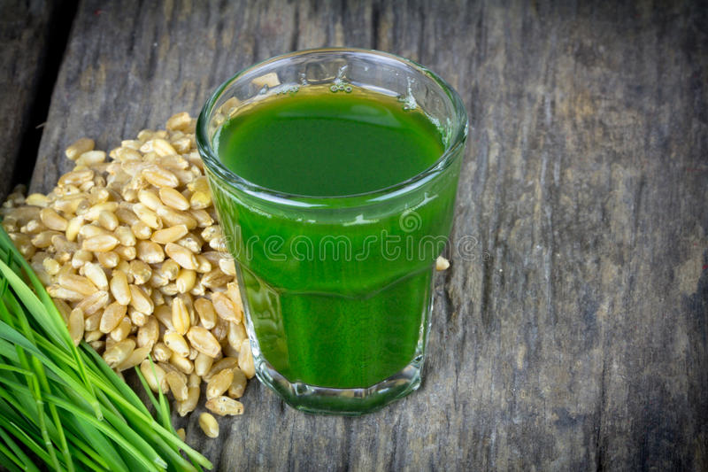 Wheat grass juice on wood background. Wheat grass juice with fresh wheat grass and wheat on wood background stock photo