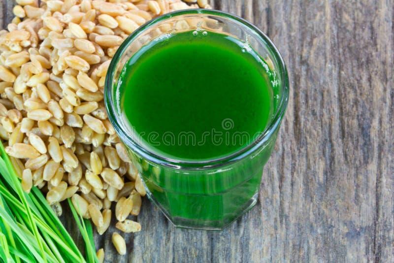 Wheat grass juice on wood background. Wheat grass juice with seed and wheat on wood background royalty free stock photos