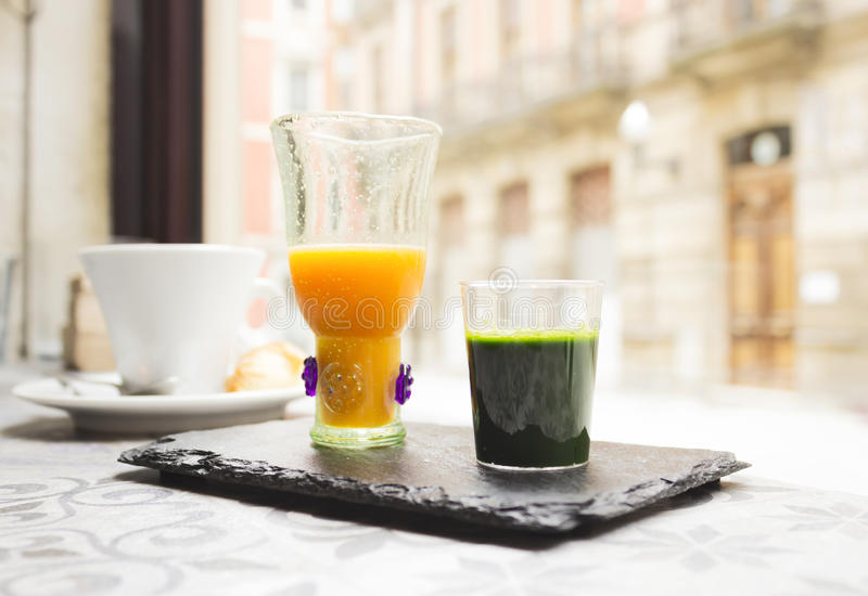 Wheat grass short and orange juice. Wheat grass shot, orange juice and coffee royalty free stock images