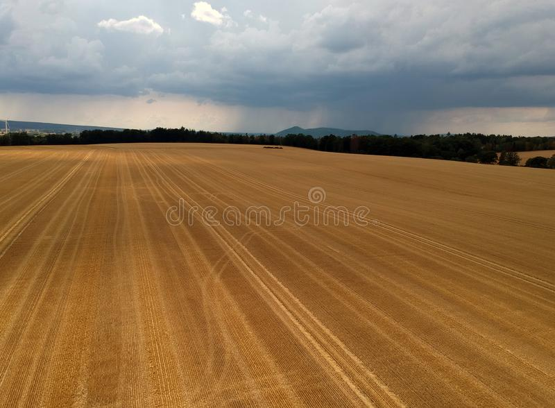 Wheat Stubble field with trees and rain clouds in the distance from the air royalty free stock image