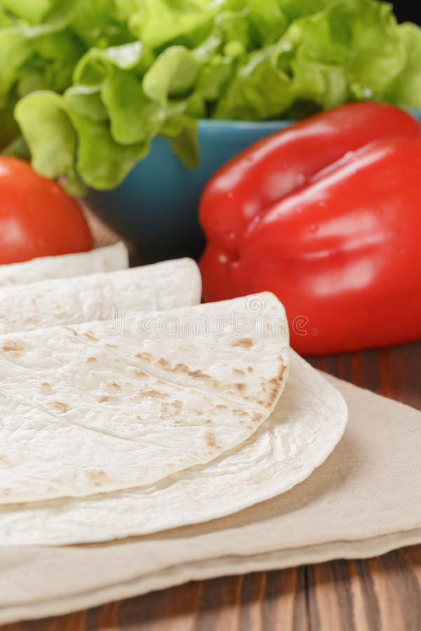 Wheat tortillas with vegetables on old wooden table stock photos