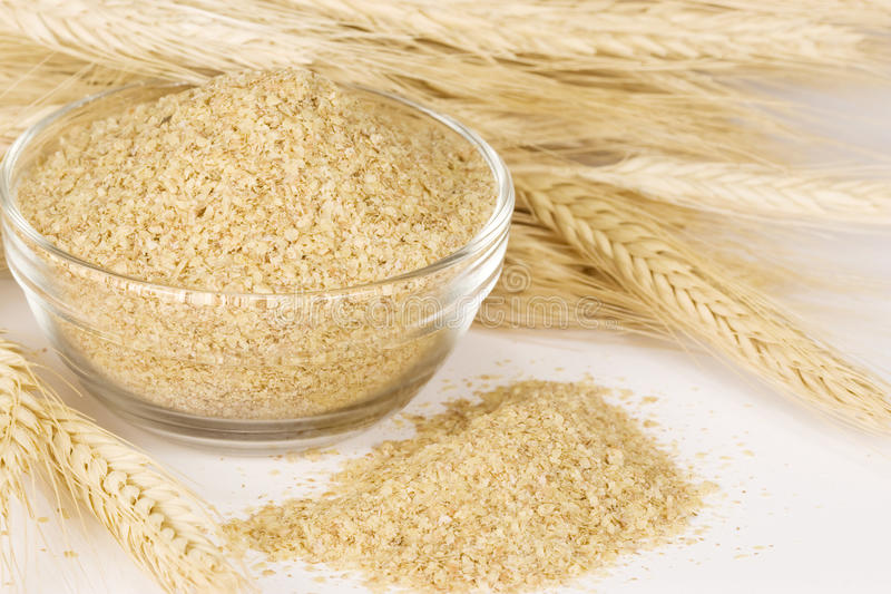 Wheat and wheatgerm. Wheat germ in glass bowl surrounded by stalks of wheat. Wheat germ is highly nutritious food as it contains more potassium and iron than any