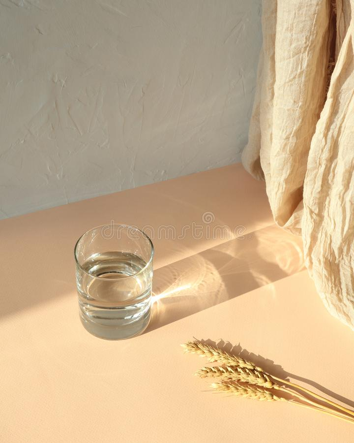 Wheatear, glas water op beige lijst met schaduw royalty-vrije stock afbeeldingen