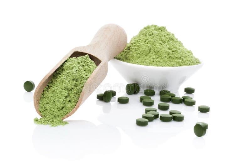 Wheatgrass powder and chlorella pills stock image