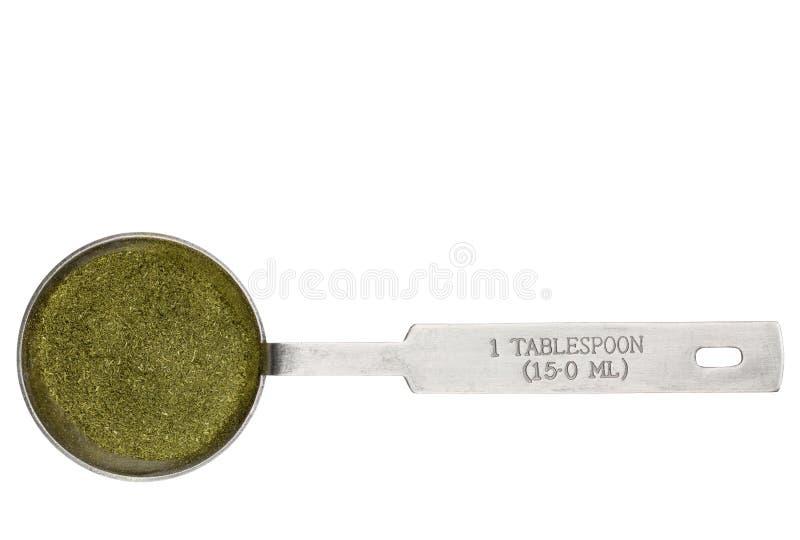Wheatgrass powder in a tablespoon. Wheatgrass powder in a metal measuring tablespoon isolated on white royalty free stock photos