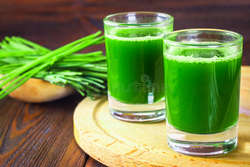 Wheatgrass shot. Juice from wheat grass. Trend of health. royalty free stock images