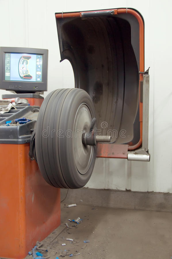 Wheel balancing. Machine in action with alu wheel royalty free stock image
