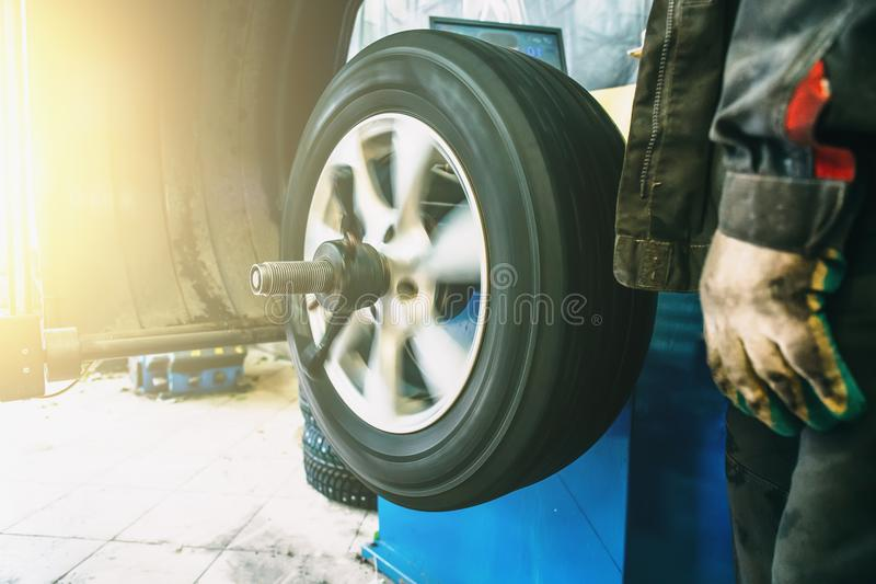 Wheel balancing or repair and change car tire at auto service garage or workshop by mechanic. Toned stock images