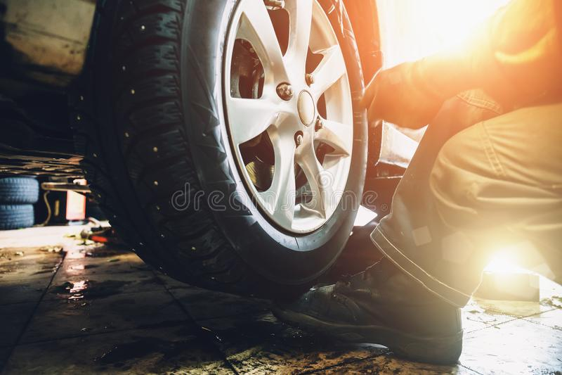 Wheel balancing or repair and change car tire at auto service garage or workshop by mechanic. Toned stock image