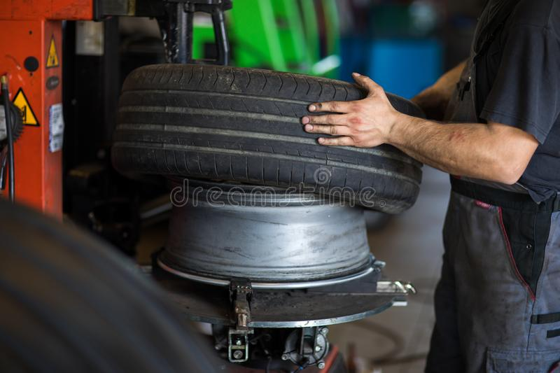 Wheel balancing or repair and change car tire at auto service. Garage or workshop by mechanic royalty free stock photo