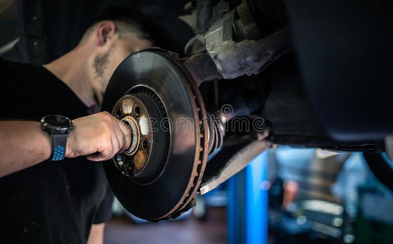 Wheel bearing repair at auto service. /garage or workshop by mechanic stock photography