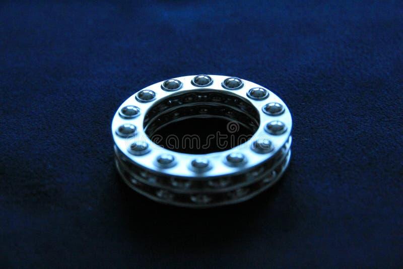 Wheel Ball Bearings Close Up. Three wheel ball bearings on dark blue felt background royalty free stock image