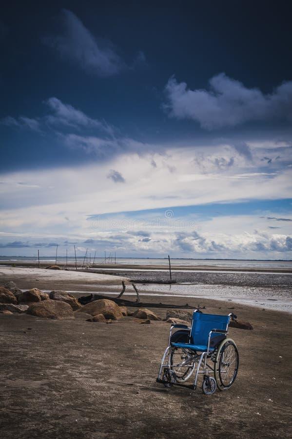 Wheel chair at the beach. An empty blue wheel chair parked on the beach stock photos