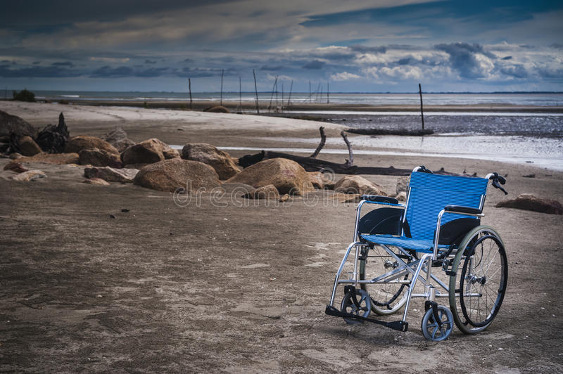 Wheel chair at the beach. An empty blue wheel chair parked on the beach royalty free stock photography
