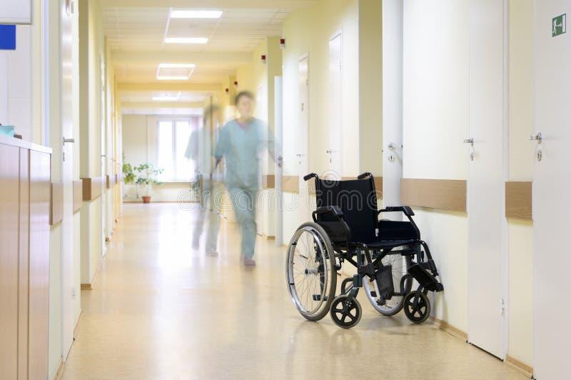 Wheel chair at corridor of hospital. Black wheel chair at the corridor of hospital. Focus on wheel chair stock photos