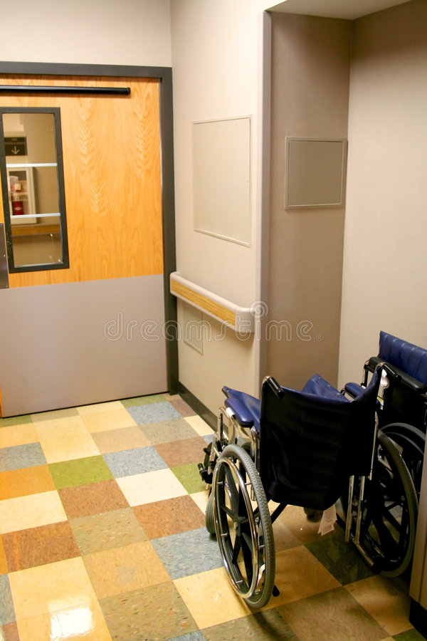 Wheel Chair In A Hospital. Wheel chair in the hospital corridor in front of entrance stock image
