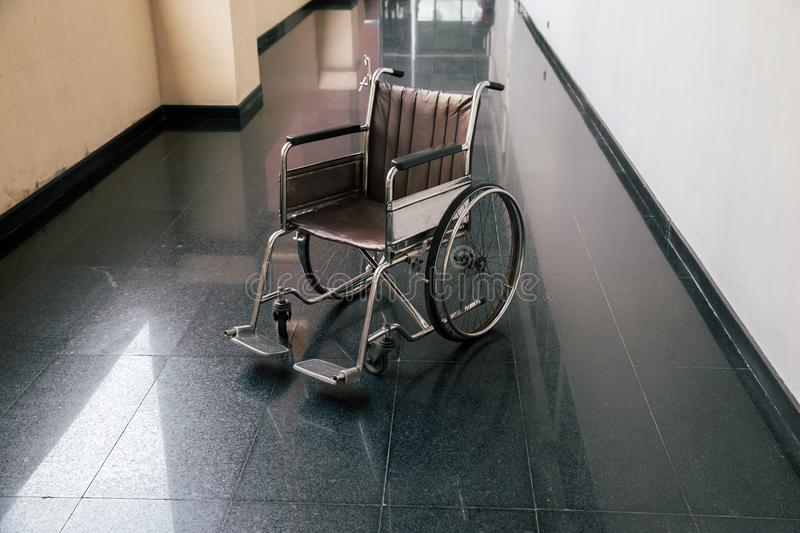 Wheel chair in the hospital corridor. Empty wheelchair parked in Patient Rooms at hospital. Empty wheelchair parked in hospital walk way royalty free stock photo