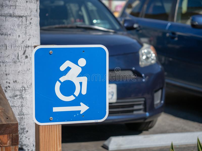 Wheel chair traffic sign pointing to the right in a parking lot. Wheel chair traffic sign pointing to the right in parking lot stock image