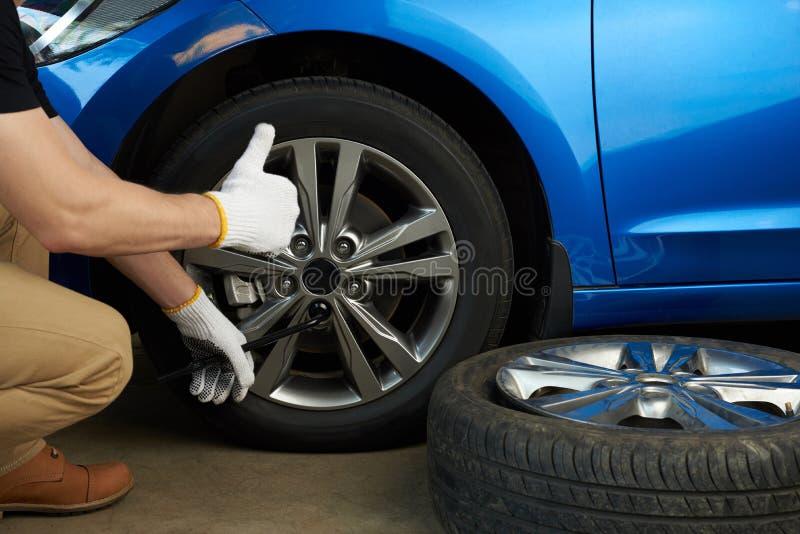 Wheel change service. Man change damage car wheel stock photo