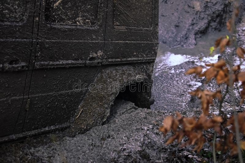 Wheel in deep puddle of mud. Dangerous expedition concept. stock image