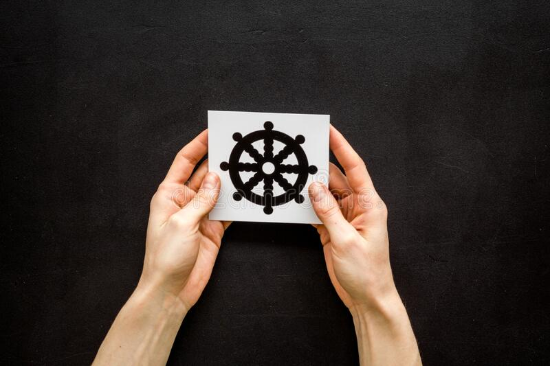 Wheel of dharma - Buddhist religion symbol - in hands on black table top view.  royalty free stock photos