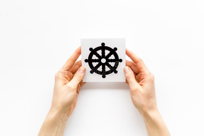 Wheel of dharma - Buddhist religion symbol - in hands on white table top view.  stock photography