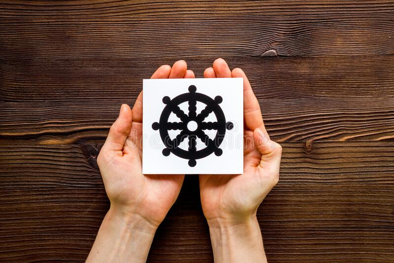 Wheel of dharma - Buddhist religion symbol - in hands on wooden table top view.  stock photography