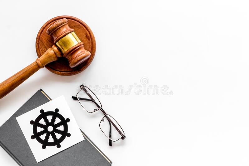 Wheel of dharma - Buddhist symbol - near gavel and book on white table. Religious conflict concept. Copy space. Wheel of dharma - Buddhist symbol - near gavel royalty free stock image