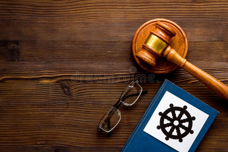 Wheel of dharma - Buddhist symbol - near gavel and book on wooden table. Religious conflict concept. Copy space. Wheel of dharma - Buddhist symbol - near gavel royalty free stock photos