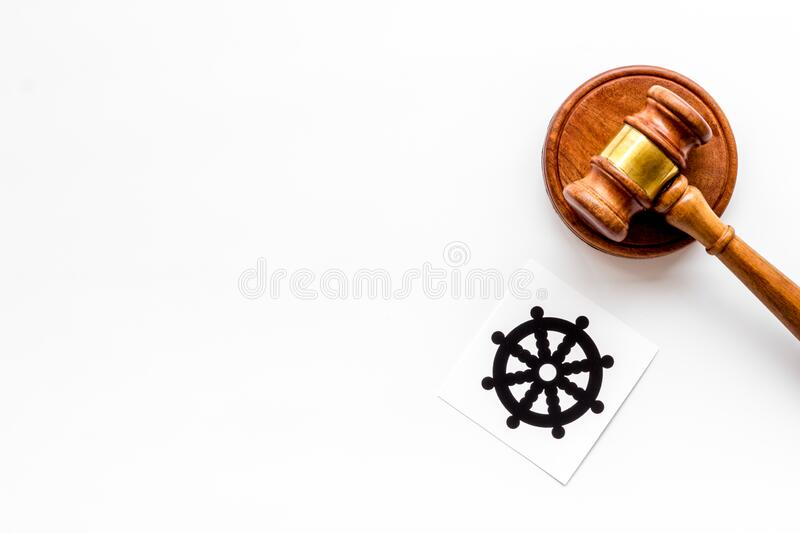 Wheel of dharma - Buddhist symbol - near gavel on white table. Religious conflict concept. Copy space. Wheel of dharma - Buddhist symbol - near gavel on white stock photo