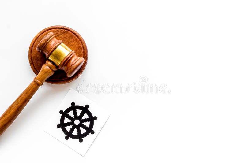 Wheel of dharma - Buddhist symbol - near gavel on white table. Religious conflict concept. Copy space. Wheel of dharma - Buddhist symbol - near gavel on white stock image