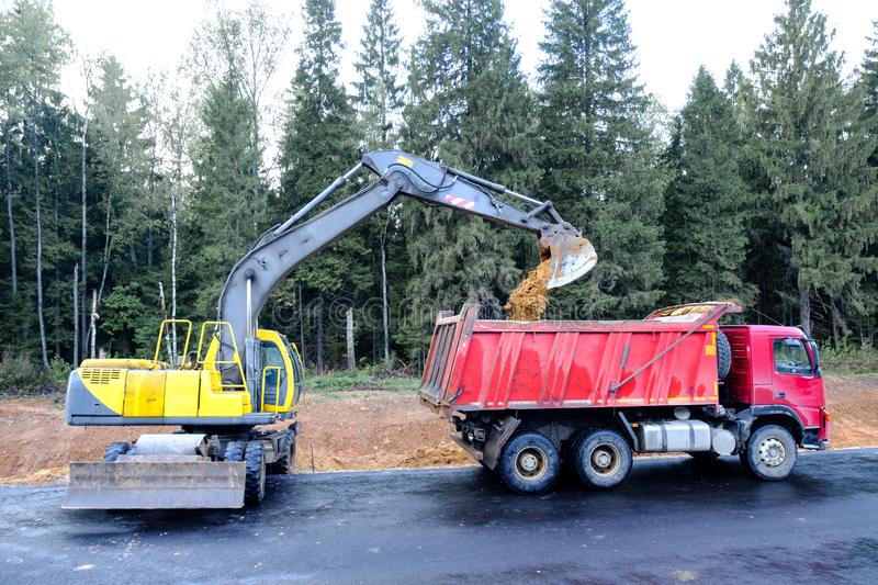The wheel excavator loads the earth with a bucket to the body of a multi-ton dump truck on the construction site.  stock photography