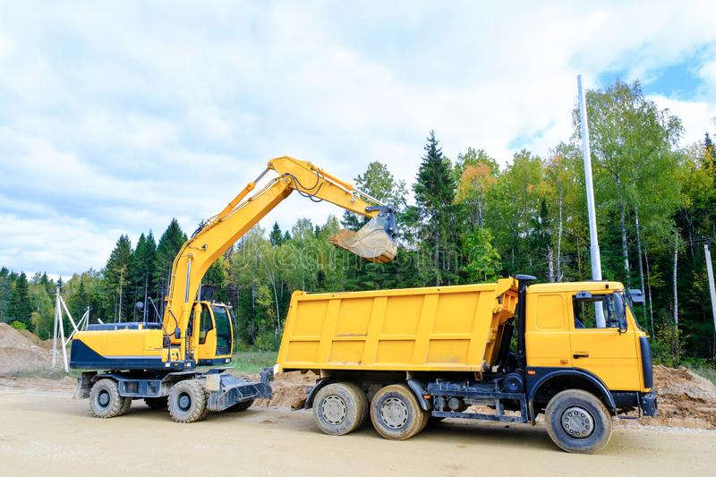 The wheel excavator loads the earth with a bucket to the body of a multi-ton dump truck on the construction site royalty free stock photography