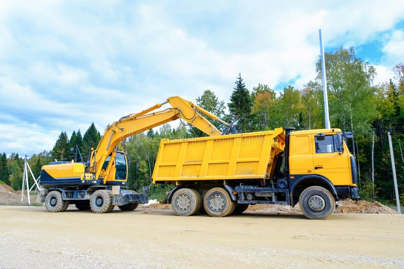 The wheel excavator loads the earth with a bucket to the body of a multi-ton dump truck on the construction site.  stock photo