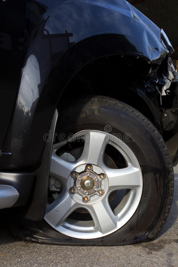 Wheel, flat tire. Side of the wheel, flat tire deflated because of an accident stock images