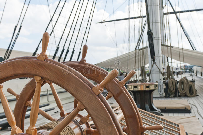 Wheel of large sailing ship. Large wooden steering wheel of an oceangoing sailing ship stock image