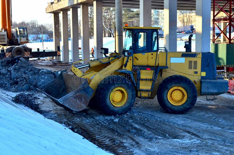 Diesel bulldozer with a bucket. Work on the dismantling of reinforced concrete slabs from the. Wheel loader on a construction site. Diesel bulldozer with a royalty free stock image