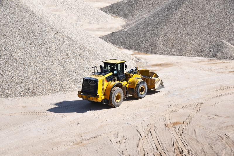 Wheel loader drives in a gravel plant and transports mined sand royalty free stock photos