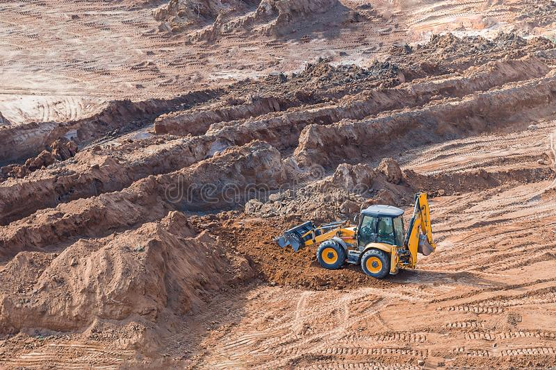 Wheel loader excavator machine working in construction site. wheel loader at sandpit during earthmoving works stock image