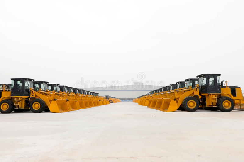 Wheel loader fleet. Lot of wheel loaders neatly parked in open space of factory stock image
