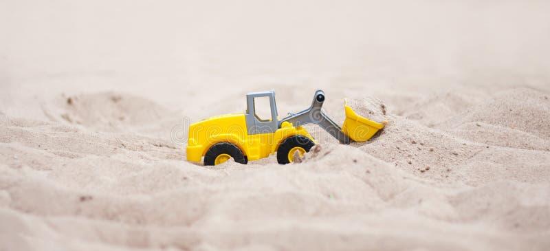 Wheel Loader. Model. Model wheel loader in the sand. Yellow wheel loader works in the sand stock images